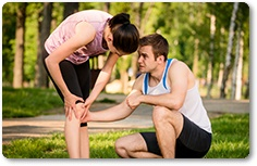 Man helps to woman with injured knee at sport activity